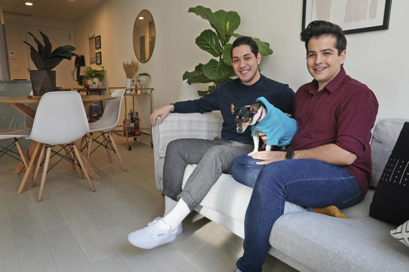 In this Monday, Nov. 25, 2019 photo, Zachariah Mohammed, left, Pete Mancilla, and their dog Remy pose for a picture in their apartment in New York. Most of the furniture in their apartment, including the couch, the table and chairs, the side table and the bar cart, are rented. Furniture-rental startups and other companies are aiming to rent furniture to millennials who don't want to commit to big purchases or move heavy furniture and are willing to pay for the convenience.   (AP Photo/Seth Wenig)