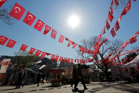 People walk past by campaign tents for the constitutional referendum in Istanbul