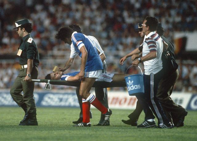 France defender Patrick Battiston is carried off the field on a stretcher as captain Michel Platini tries to comfort him during the World Cup semi-final against West Germany in Seville, on July 8, 2014 (AFP Photo/)