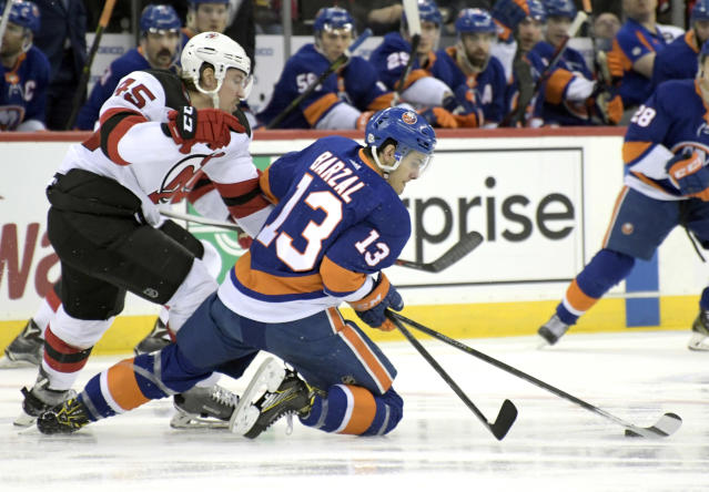 New Jersey Devils defenseman Sami Vatanen (45) and New York Islanders center Mathew Barzal (13) vie for the puck during the first period of an NHL hockey game Saturday, Feb. 24, 2018, in Newark, N.J. (AP Photo/Bill Kostroun)