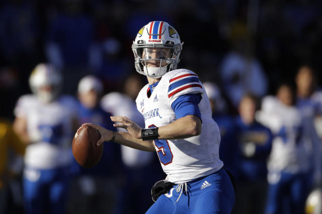 Kansas quarterback Carter Stanley (9) looks for a receiver during the first half of an NCAA college football game against Baylor, Saturday, Nov. 30, 2019, in Lawrence, Kan. (AP Photo/Charlie Riedel)