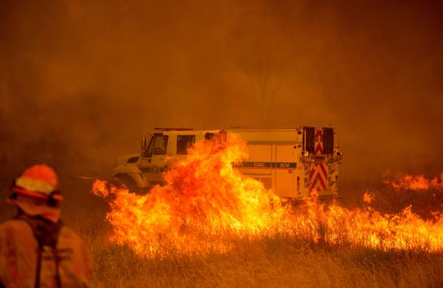 <p>A fire vehicle is surrounded by flames as the Pawnee fire jumps across highway 20 near Clearlake Oaks, Calif. on July 1, 2018. (Photo: Josh Edelson/AFP/Getty Images) </p>
