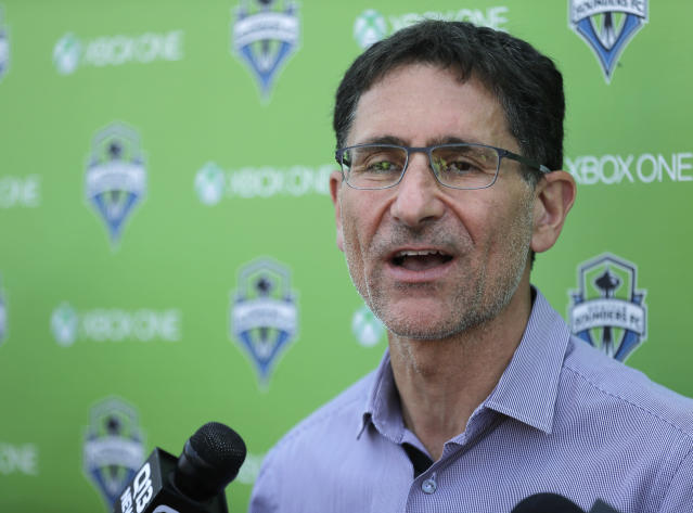 FILE - In this Aug. 29, 2018, file photo, MLS soccer Seattle Sounders majority owner Adrian Hanauer talks to reporters in Tukwila, Wash. The Sounders announced Tuesday, Aug. 13, 2019, that they are adding Seattle Seahawks quarterback Russell Wilson and several others to the club's ownership group, as Hollywood producer Joe Roth leaves the franchise. (AP Photo/Ted S. Warren, File)