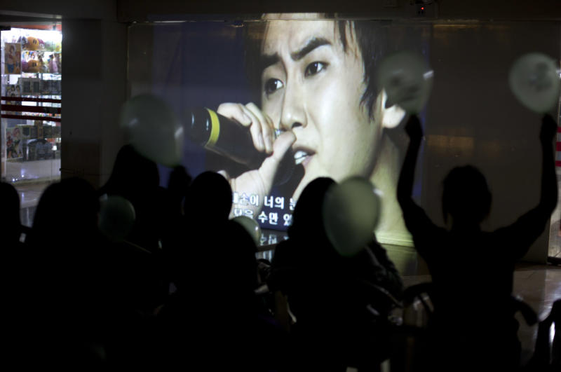 """In this May 18, 2013 photo, fans of South Korean K-pop singer Heo Young Saeng watch his video play in a viewing area inside a shopping mall in Lima, Peru. """"Although you won't believe it, in Peru the K-pop groups are starting to be more popular than Justin Bieber, Lady Gaga or Demi Lovato,"""" said Diana Rodriguez, who is capitalizing on the trend by organizing Korean dance contests throughout Peru. (AP Photo/Martin Mejia)"""