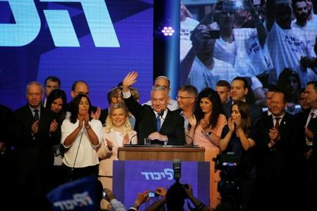 Israeli Prime Minister Benjamin Netanyahu stands next to his wife Sara as he waves to supporters at his Likud party headquarters following the announcement of exit polls during Israel's parliamentary election in Tel Aviv, Israel