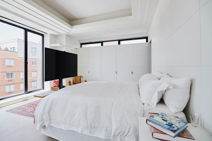 The bedroom's custom floating TV was designed to preserve space without obstructing the city view. The Parisian-style white cabinetry is yet another continuation of that design element.