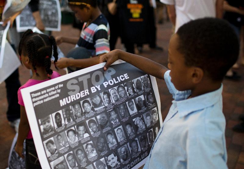 Children look at posters calling for an end to police violence in Baltimore, Maryland on May 10, 2015 (AFP Photo/Andrew Caballero-Reynolds)