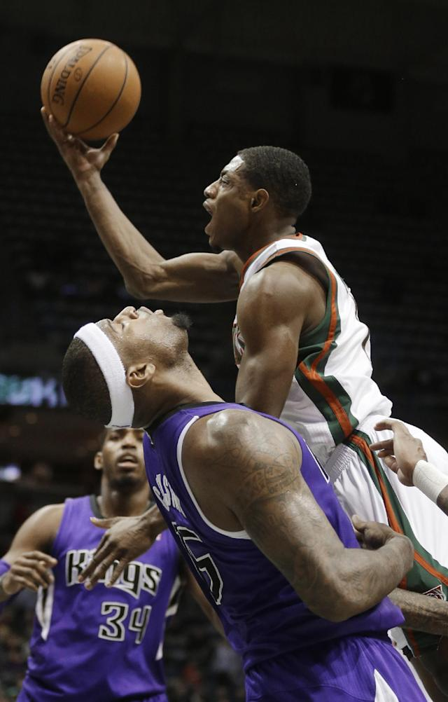 Milwaukee Bucks' Brandon Knight puts up a shot against Sacramento Kings' DeMarcus Cousins during the second half of an NBA basketball game Wednesday, March 5, 2014, in Milwaukee. (AP Photo/Jeffrey Phelps)