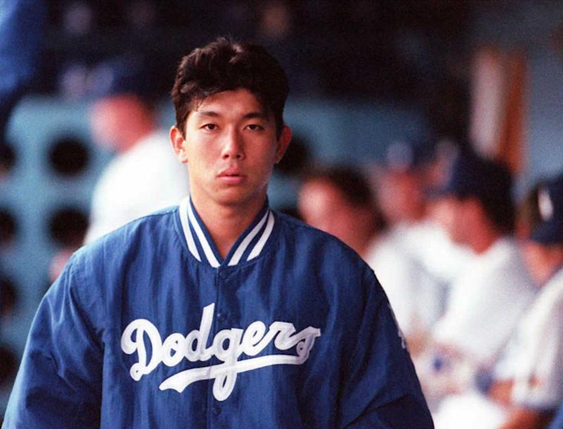 Hideo Nomo, wearing a Dodgers jacket, walks in the dugout during a 1995 game.