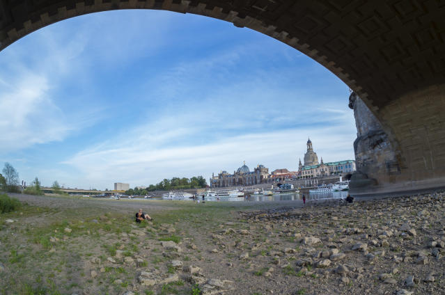 <p>A low water level of Elbe river is seen below Dresden's old town district during hot weather on Aug. 7, 2018 in Germany. A heat wave and dry spell are persisting over Germany that this week is bringing temperatures to 38 degrees Celsius. Farmers are reporting plummeting harvests, while shrinking rivers are exposing munitions left over from World War II. (Photo: Matthias Rietschel/Getty Images) </p>