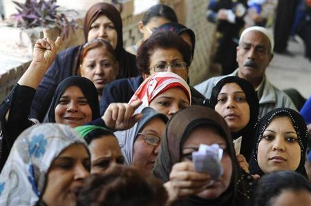 Women queue outside a polling centre to vote in a referendum on Egypt's new constitution in Cairo
