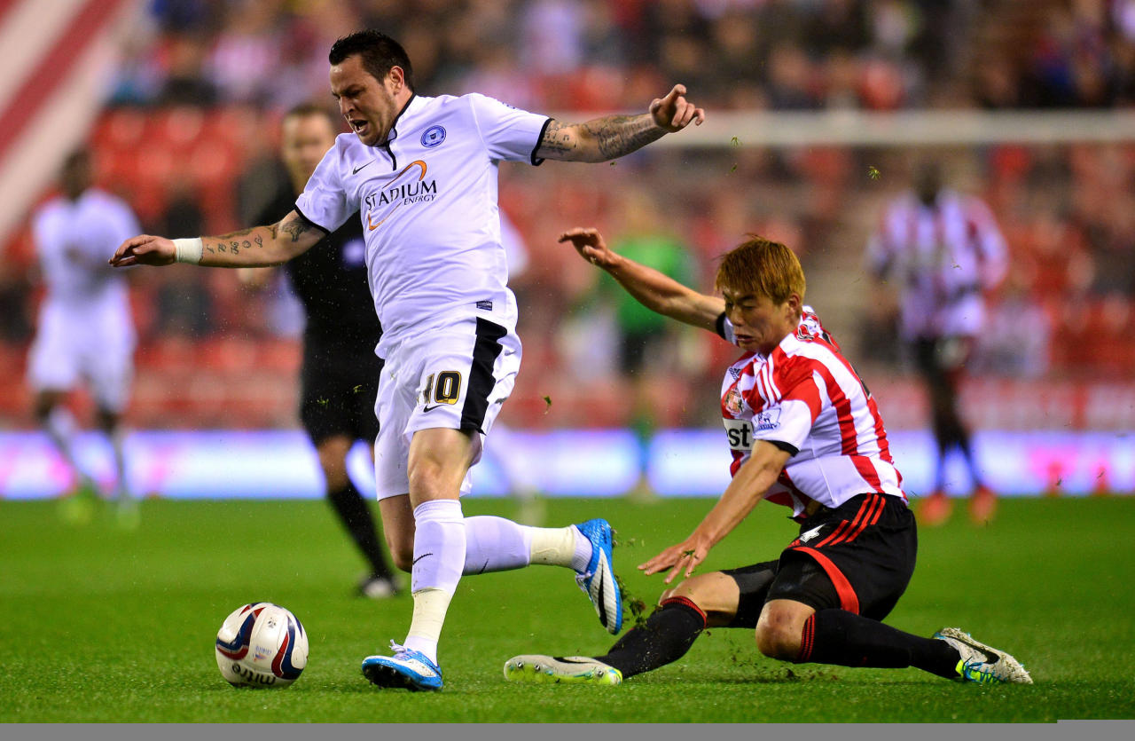 Sunderlands Ki Sung Yueng (right) fouls Peterborough's Lee Tomlin during the Capital One Cup, Third round match at the Stadium of Light, Sunderland.