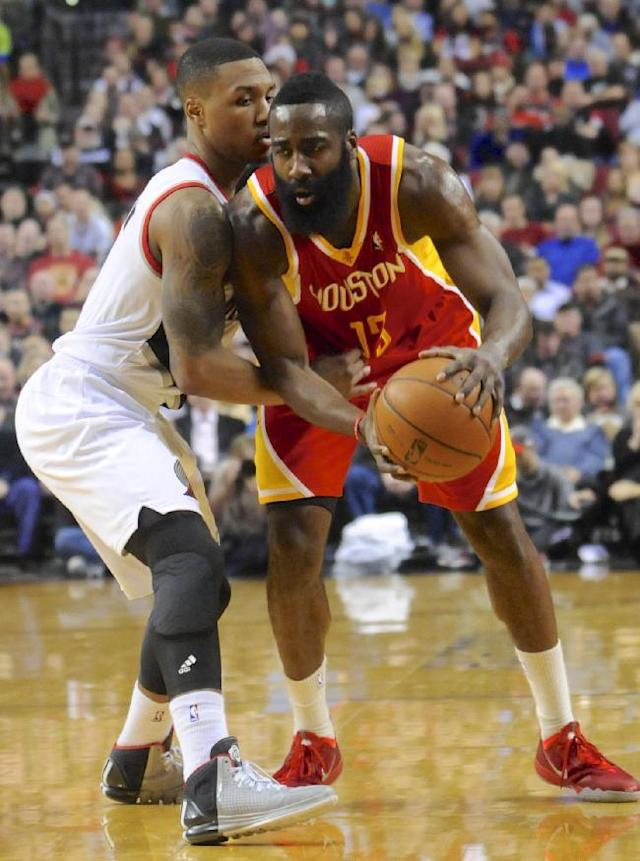 Houston Rockets' James Harden (13) looks to pass against Portland Trail Blazers' Damian Lillard (0) during the first half of an NBA basketball game in Portland, Ore.,Thursday Dec. 12, 2013. (AP Photo/Greg Wahl-Stephens)