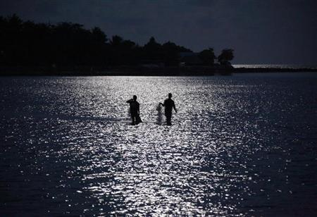 Fishermen are illuminated by the full moon as they prepare to cats their nets near the village of Teaorereke located on South Tarawa in the central Pacific island nation of Kiribati