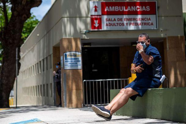 PHOTO: A man wearing a surgical mask sits in front of the emergency room entrance of the Ashford Presbyterian Community Hospital in San Juan, Puerto Rico on March 21, 2020. (Ricardo Arduengo/AFP via Getty Images, FILE)