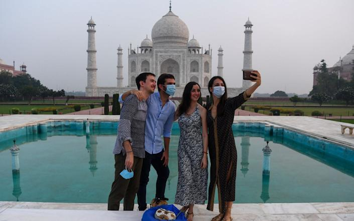The Taj Mahal in Agra reopened to visitors today in a symbolic business-as-usual gesture, even as India looks set to overtake the US as the global leader in coronavirus infections - SAJJAD HUSSAIN/AFP