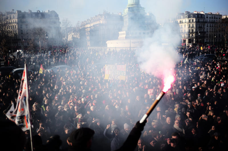 A worker holds a flare after a crowd on the Place de la Bastille listened to striking musicians of the Paris Opera house performing outside the Bastille Opera house Tuesday, Dec. 31, 2019 in Paris. (AP Photo/Kamil Zihnioglu)