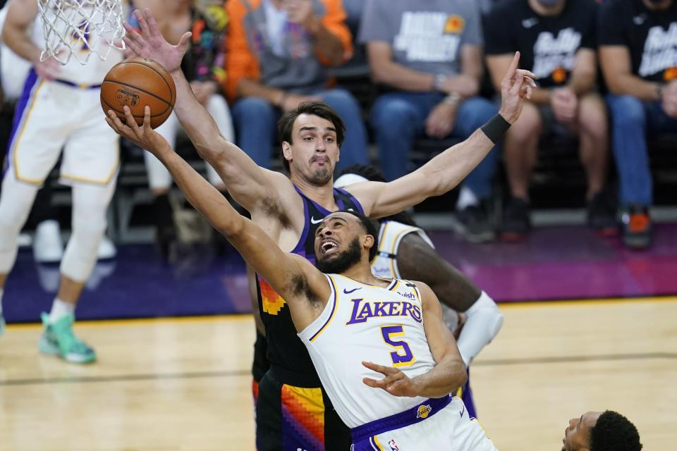 Los Angeles Lakers guard Talen Horton-Tucker (5) drives past Phoenix Suns forward Dario Saric to score during the first half of Game 1 of their NBA basketball first-round playoff series Sunday, May 23, 2021, in Phoenix. (AP Photo/Ross D. Franklin)