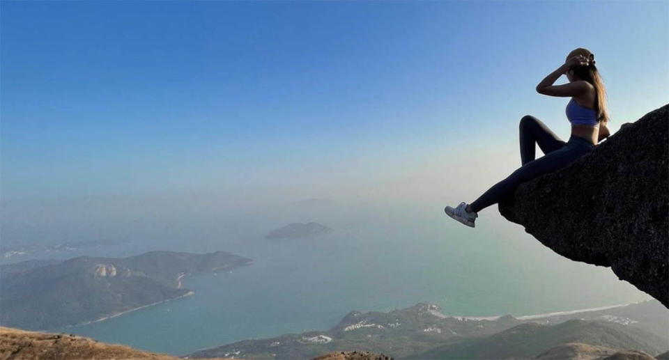 Sofia Cheung is pictured sitting on the edge of a rock edge. The influencer was known for her risky photos.