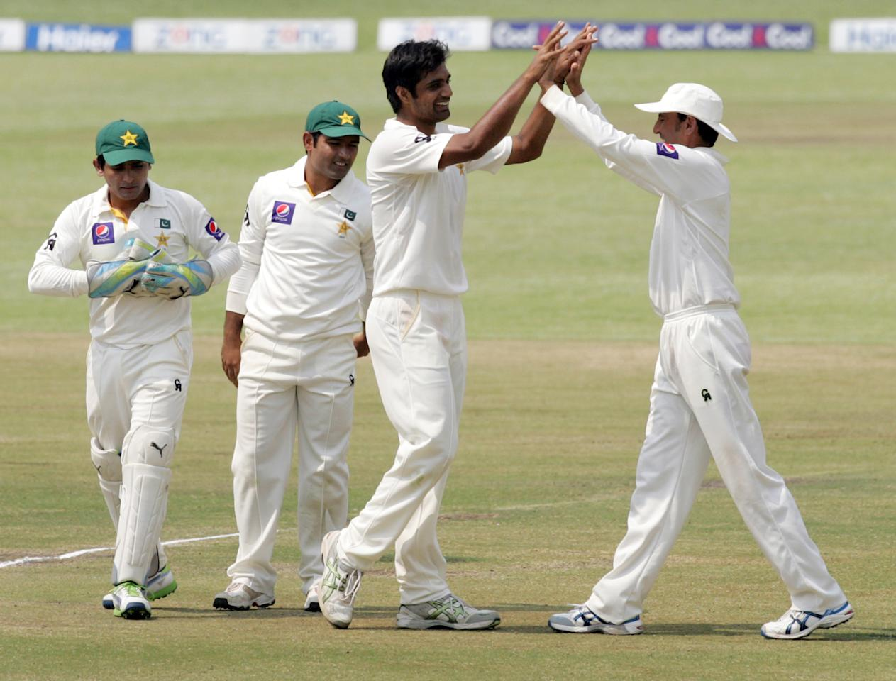 Pakistan's players congratulate their teammate bowler Rahat Ali (C) for a wickket during the fourth day of the second cricket test match between Pakistan and hosts Zimbabwe at the Harare Sports Club on September 13, 2013.  AFP PHOTO / JEKESAI NJIKIZANA        (Photo credit should read JEKESAI NJIKIZANA/AFP/Getty Images)