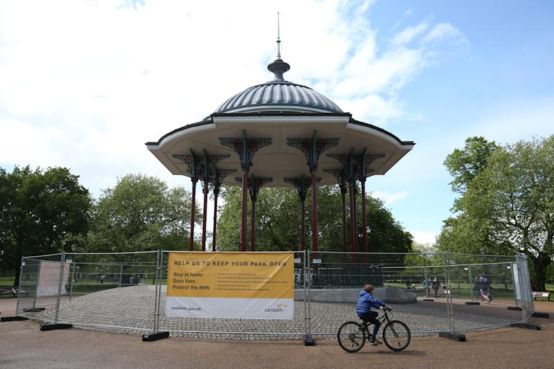 A young cyclist passes the closed off bandstand at Clapham Common, south London, as the UK continues in lockdown to help curb the spread of the coronavirus.