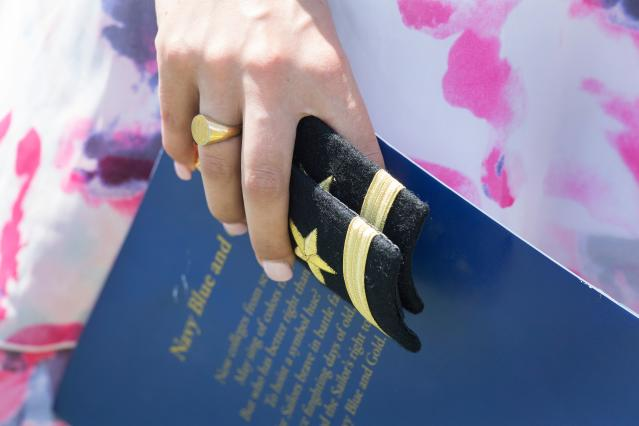 <p>A family member holds the shoulder boards for a United States Naval Academy graduate during a ceremony in Annapolis, Md., on May 25, 2018. (Photo: Jim Watson/AFP/Getty Images) </p>