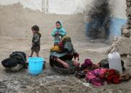 An internally displaced Afghan woman washes clothes outside her shelter on the outskirts of Kabul