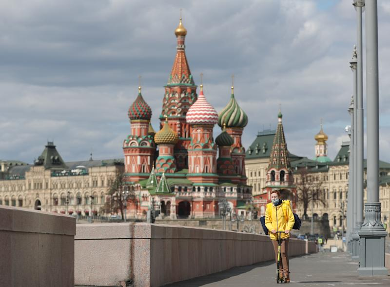 A courier of the Yandex.Eda food delivery service riding a bicycle in Bolshoi Moskvoretsky Bridge overlooking St Basil's Cathedral during the ongoing COVID-19 coronavirus pandemic