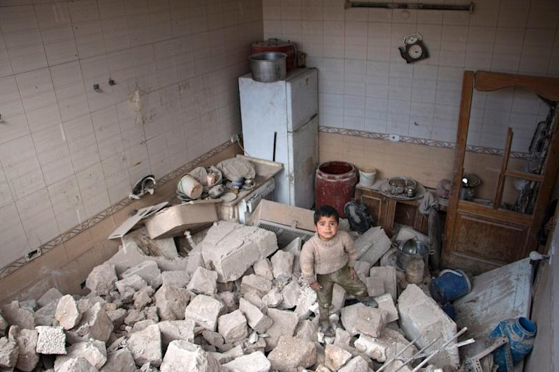 A Syrian child stands amid rubble in his family's home in Aleppo on April 19, 2015 after an airstrike (AFP Photo/Karam al-Masri)