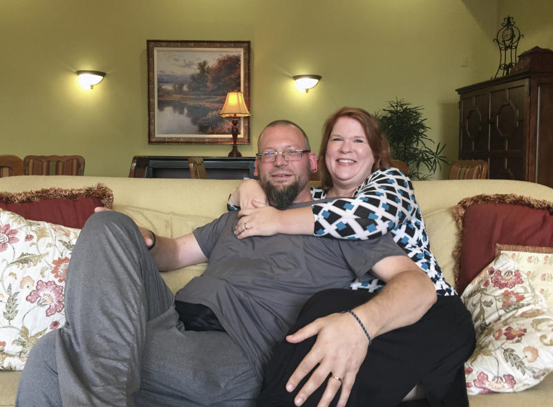 David and Elizabeth Weinlick, poses for a photo at their home, Wednesday, Aug. 16, 2017, in Woodbury, Minn. The Minnesota couple who began their life together through an arranged marriage nearly 20 years ago are about to renew their vows. For David and Elizabeth, Friday's ceremony will happen at the Mall of America. It's the same place where David's friends chose Elizabeth to be his bride in a spectacle that drew national headlines. The occasion will also be tinged with sadness. David Weinlick has been diagnosed with terminal cancer. (AP Photo/Kyle Potter)