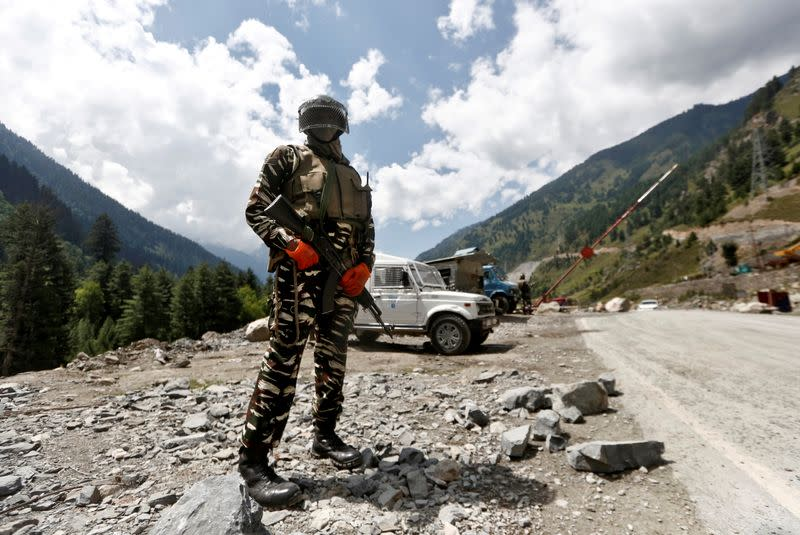 FILE PHOTO: An Indian Central Reserve Police Force personnel stands guard at a checkpoint along a highway leading to Ladakh, at Gagangeer