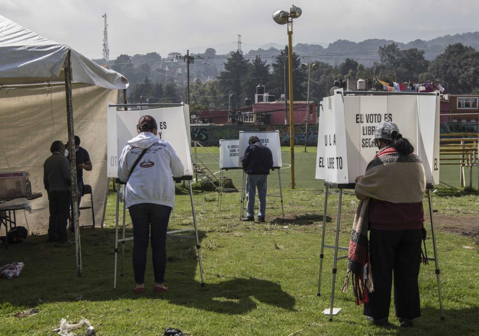 People cast their votes in a non-binding referendum on whether Mexican ex-presidents should be tried for any illegal acts during their time in office, in San Miguel Topilejo, Mexico City Sunday, August 1, 2021. (AP Photo/Christian Palma)