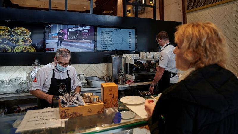 Masked chef prepares food for customer in fast-casual restaurant
