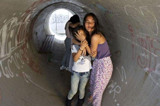 Israelis take cover in a concrete shelter in Nitzan, south of the coastal city of Ashdod during a rocket attack