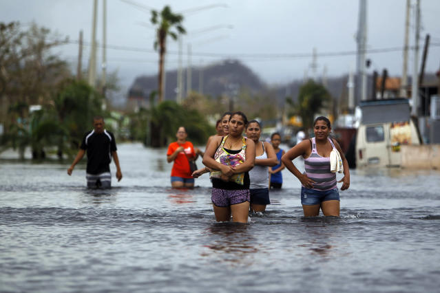 <p>People walk on a flooded street in the aftermath of Hurricane Maria in San Juan, Puerto Rico on Sept. 22, 2017. (Photo: Ricardo Arduengo/AFP/Getty Images) </p>