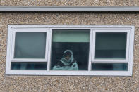 A woman looks out a window from a locked-down public housing tower in Melbourne, Monday, July 6, 2020. As Australia is emerging from pandemic restrictions, the Victoria state capital Melbourne is buckling down with more extreme and divisive measures that are causing anger and igniting arguments over who is to blame as the disease spreads again at an alarming rate. (AP Photo/Andy Brownbill)