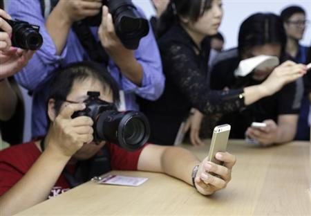 A photographer holds up a new iPhone 5S to take a photo of it at Apple Inc's announcement event in Beijing, September 11, 2013.