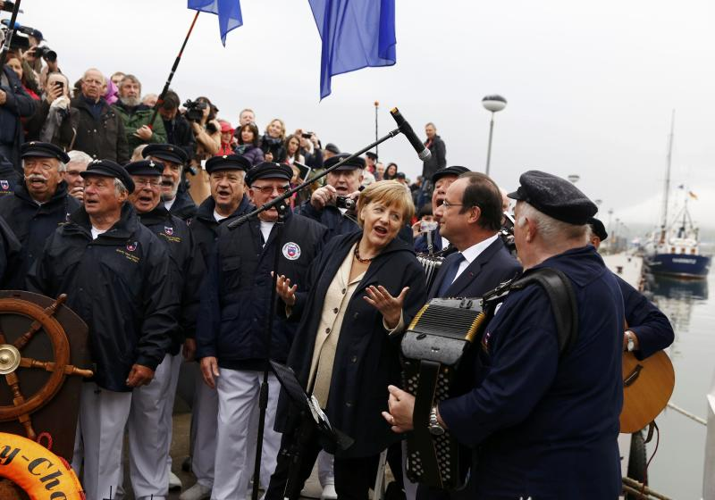 German Chancellor Angela Merkel, 3rd right, and French President Francois Hollande, 2nd right, listen to a Shanty choir before embarking on the ship Nordwind in Sassnitz on Ruegen island in the Baltic sea, Germany, Friday, May 9, 2014. (AP Photo/Thomas Peter, Pool)