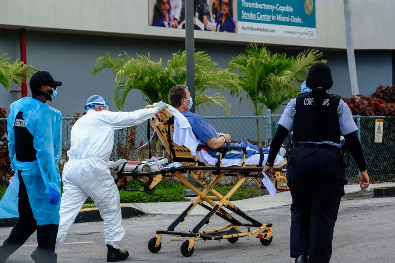 Emergency Medical Technicians (EMT) arrive with a correctional patient at North Shore Medical Center where the coronavirus disease (COVID-19) patients are treated, in Miami