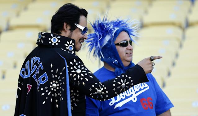 "Los Angeles Dodgers fans, including Danny ""Elvez"" Del Toro, left, watch batting practice before Game 4 of the National League division baseball series between the Dodgers and the Atlanta Braves, Monday, Oct. 7, 2013, in Los Angeles. (AP Photo/Danny Moloshok)"