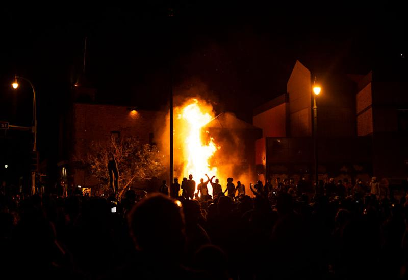 Pictured are protesters cheering as the Third Police Precinct burns behind them in Minneapolis.