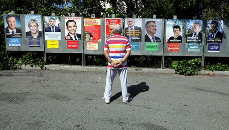 FILE PHOTO: A man looks at campaign posters of the 11th candidates who run in the 2017 French presidential election in Saint Andre de La Roche