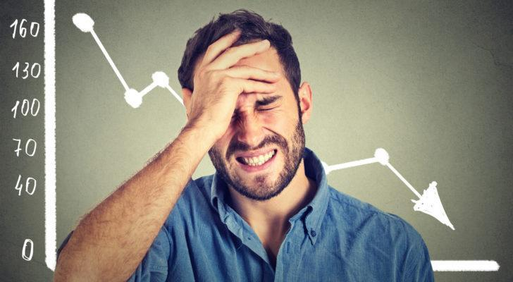 Man holding head with a falling chart in the background.
