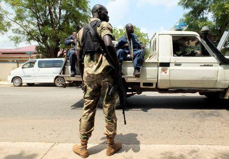 A Sudan People's Liberation Movement (SPLM) soldier stands guard as a police truck patrols following the recent fighting outside the Presidential State House in South Sudan's capital Juba, July 14, 2016. REUTERS/Stringer