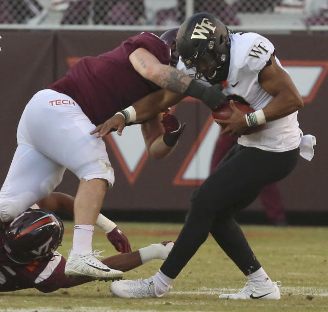 Wake Forest quarterback Jamie Newman (12) is sacked by Virginia Tech defender Jarrod Hewitt (5) in the second quarter of an NCAA college football game Saturday, Nov. 9, 2019, in Blacksburg, Va. (Matt Gentry/The Roanoke Times via AP)