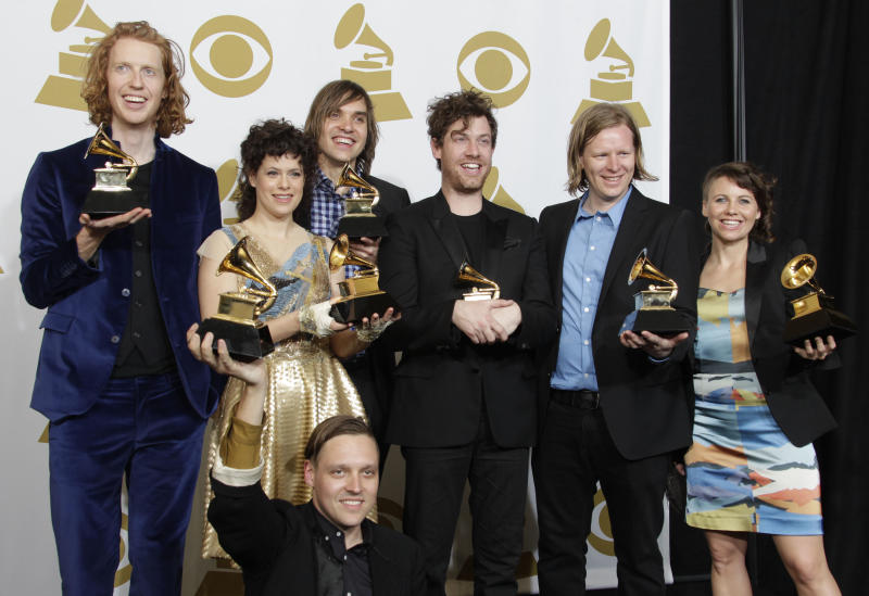"FILE - Arcade Fire pose backstage with the award for album of the year at the 53rd annual Grammy Awards on in this Feb. 13, 2011 file photo taken, in Los Angeles. The Canadian musicians thanked the members of Rara Lakay in a smattering of Haitian Creole, and building on their beats launched into songs from a new album heavily influenced by Haiti's unique rhythms Thursday Oct. 24, 2013. The Thursday night show at the Little Haiti Cultural Center was the second of two Miami performances this week that billed the band as ""The Reflektors."" Arcade Fire's new album ""Reflektor"" comes out next week. (AP Photo/Jae C. Hong, File)"