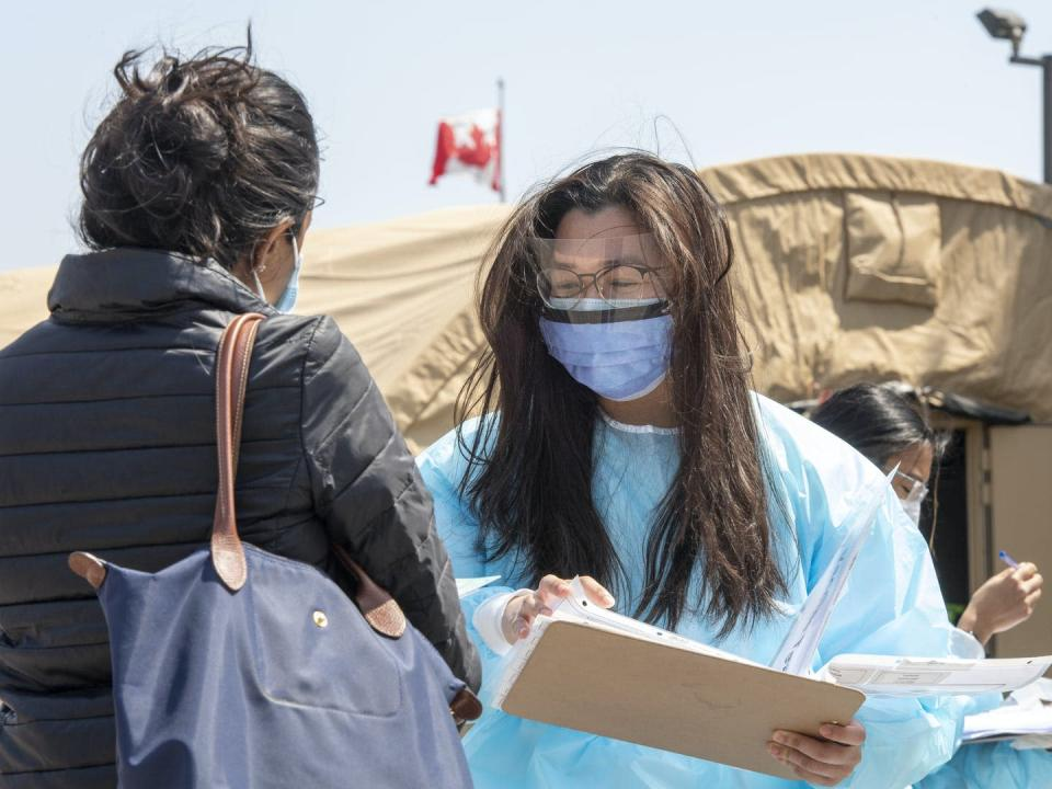"""<span class=""""caption"""">Intake workers assist visitors at an immigrant and refugee vaccine clinic set up by Global Medic in Toronto in April. Research suggests racialized immigrant women earn less money than other groups, regardless of how much training, education or networking they do.</span> <span class=""""attribution""""><span class=""""source"""">THE CANADIAN PRESS/Frank Gunn</span></span>"""