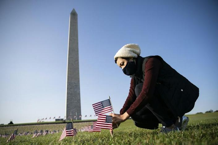A woman places a flag at a memorial on the National Mall in Washington for the more than 200,000 people in the United States who have died of Covid-19