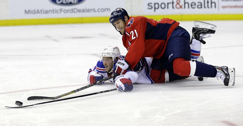 Washington Capitals center Brooks Laich (21) goes over a diving New York Rangers right wing Ryan Callahan in the second period of an NHL hockey game, Wednesday, Oct. 16, 2013, in Washington. (AP Photo/Alex Brandon)