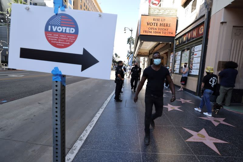 People walk on Hollywood Boulevard outside the Pantages Theater polling station, during the global outbreak of the coronavirus disease (COVID-19), in Hollywood, Los Angeles